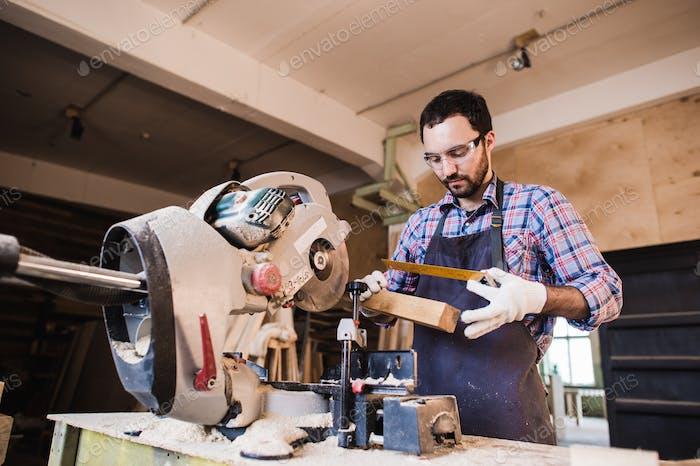 Schreiner arbeitet an einer elektrischen Summen Säge Schneiden einige Bretter, er trägt Schutzbrille
