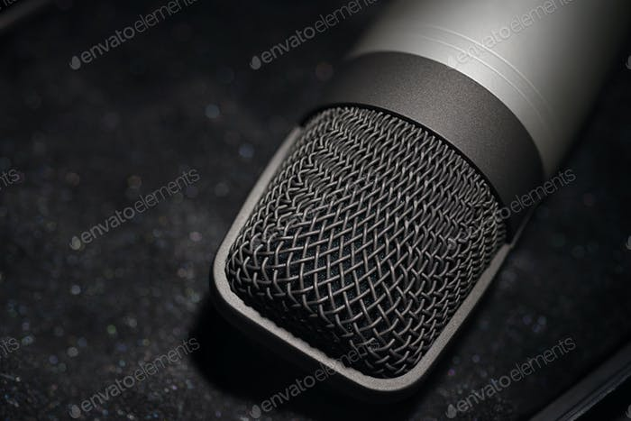 Silver studio condenser microphone on black soft foam