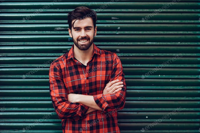 Young smiling man, model of fashion, wearing a plaid shirt with