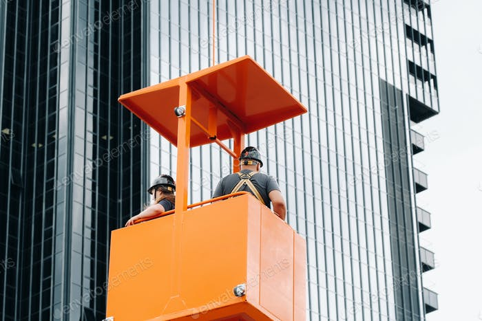 Workers in a construction cradle climb on a crane to a large glass building.The crane lifts the