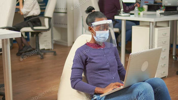 Black freelancer with protection mask analysing project on laptop