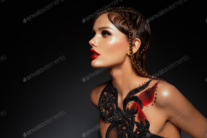 Beautiful young model with red lips and body art