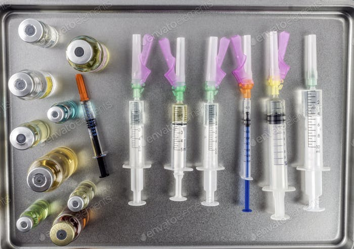 Syringes loaded with medication next to medicine vials prepared in hospital