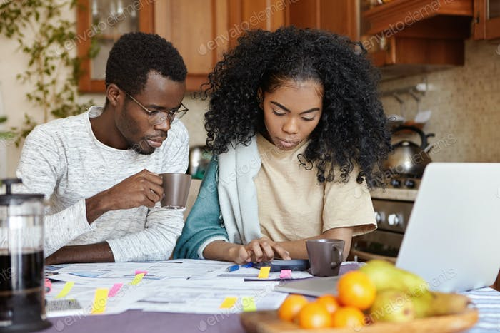 Finances and family budget concept. Indoor shot of serious African girl using calculator while payin