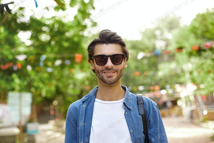 Good looking young dark haired male with beard wearing casual clothes and sunglasses