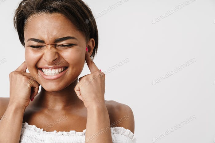 Image of joyful african american woman laughing and plugging her ears