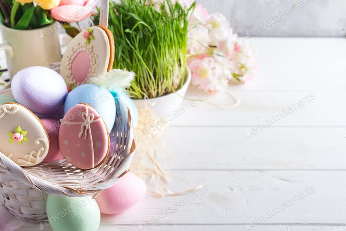 Easter greeting card with glazed cookies and colorful easter eggs in basket . With copy space