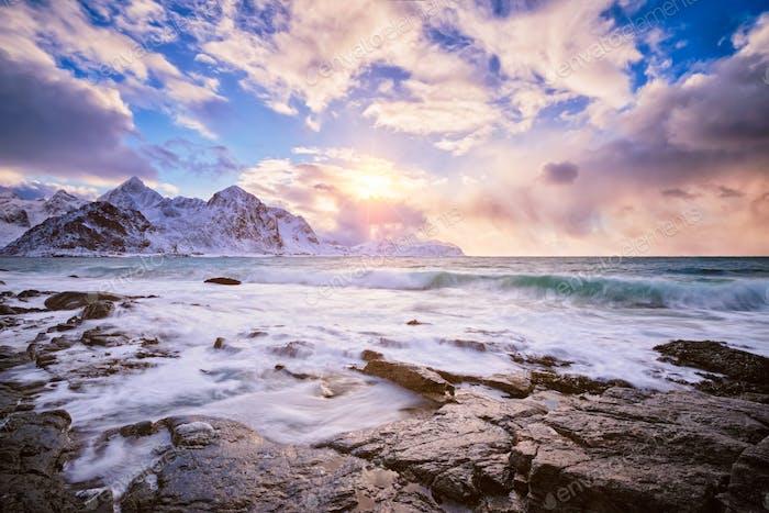 Coast of Norwegian sea on rocky coast in fjord on sunset