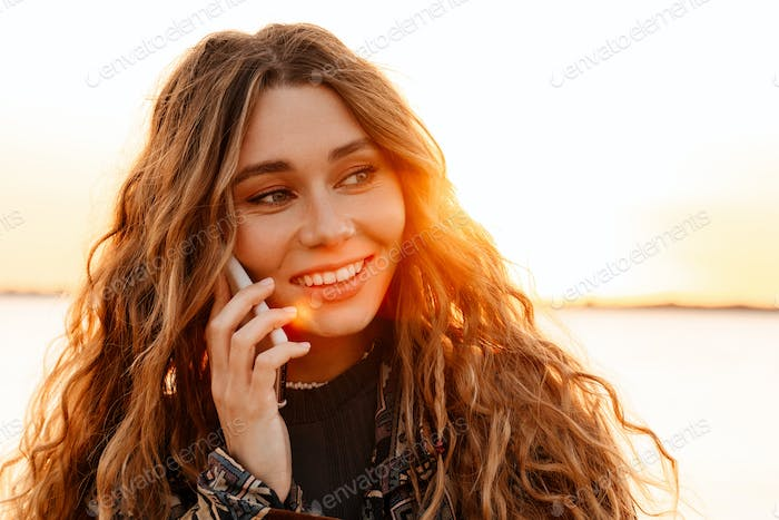 Cheery young woman talking by smartphone