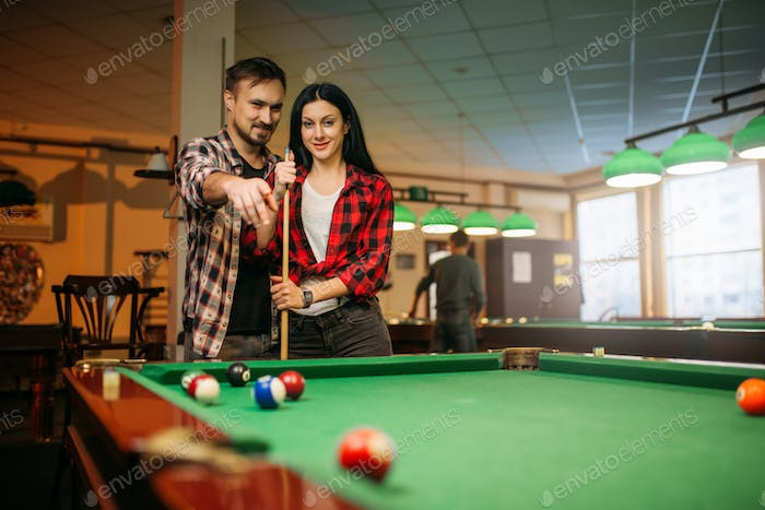 Male and female billiard players with cue