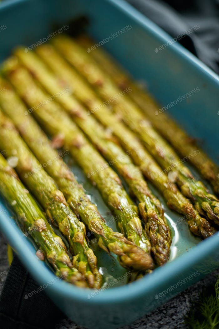 Close up with selective focus on roasted asparagus seasoned with salt, pepper, garlic