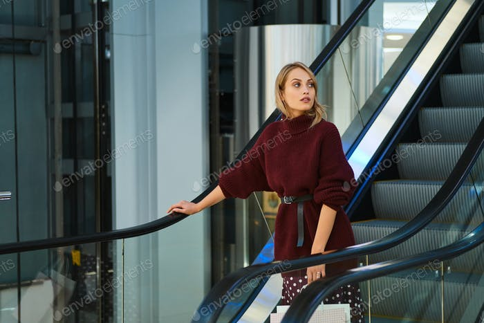 Beautiful blond girl with shopping bags on escalator dreamily looking away in modern shopping mall