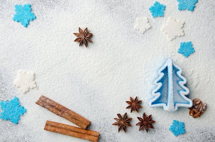 Christmas kitchen background made of flour, cinnamon sticks, anise,  cookie cutter