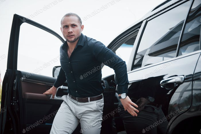 Portrait of a young bodyguard near the car. He performs dangerous work