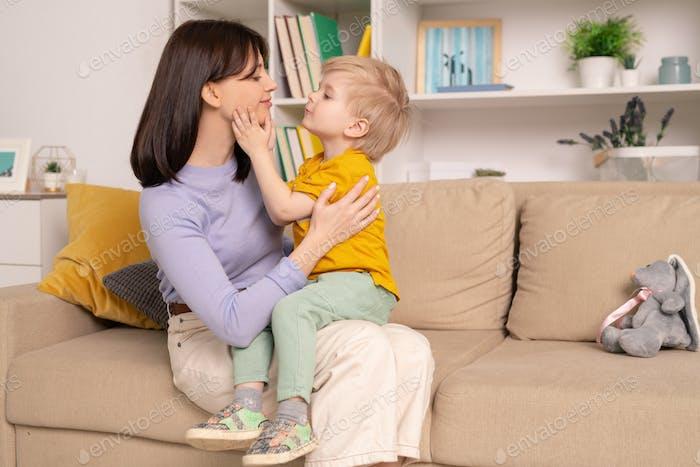 Glückliche junge liebevolle Mutter und ihr kleiner Sohn Ausdruck Liebe zu einander