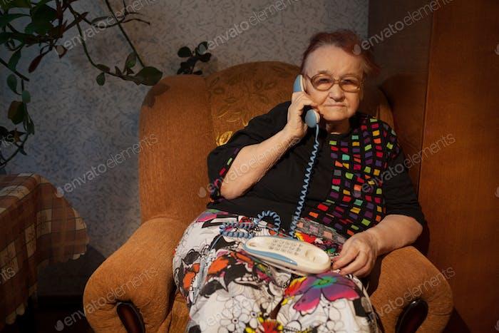 Ältere Frau im Gespräch auf dem Telefon zu Hause
