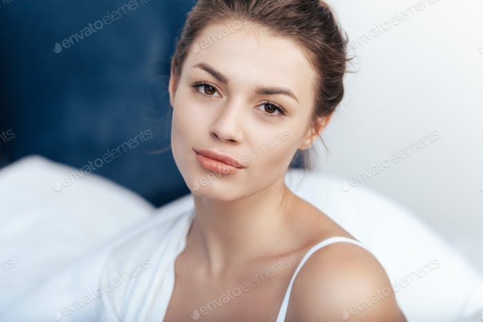 Close-up portrait of charming young woman in bed