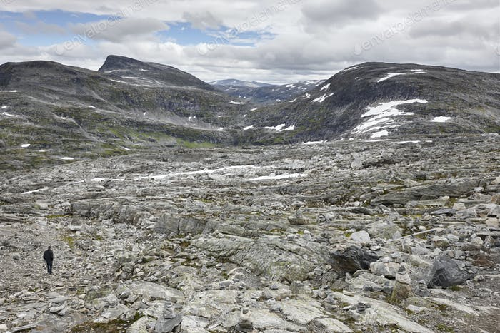 Norwegian rocky mountain landscape with snow and hiker. Norway trekking. Horizontal