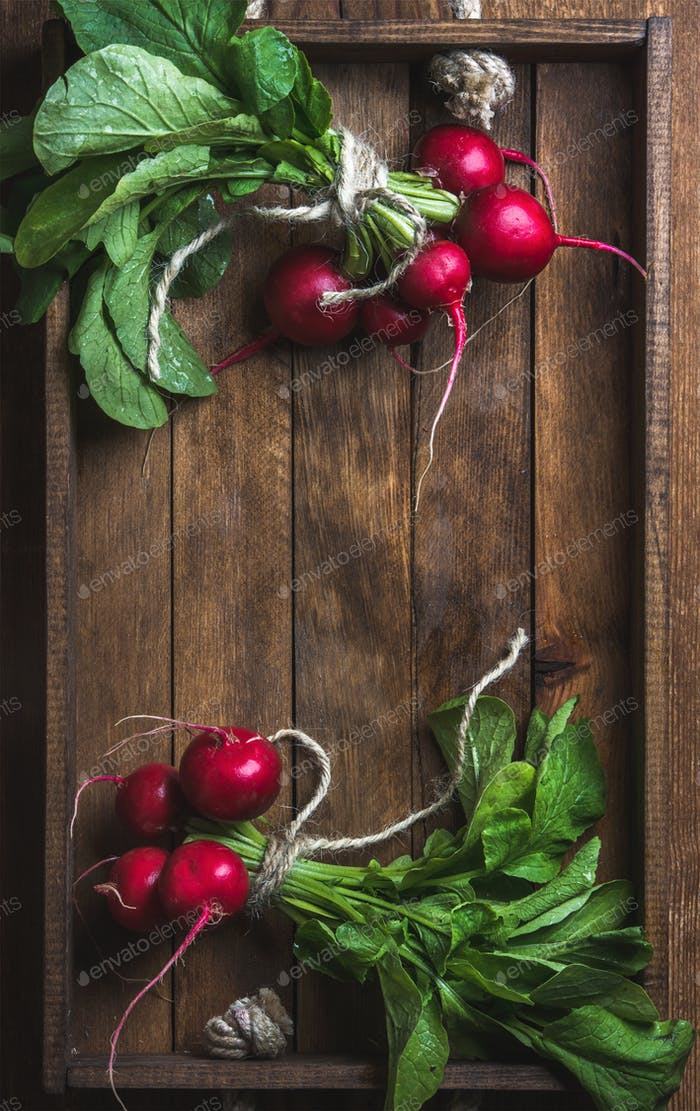 Fresh radish banches on wooden tray background, copy space