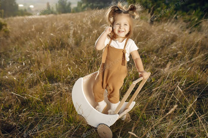 Cute little girl playing in a park with white carriage