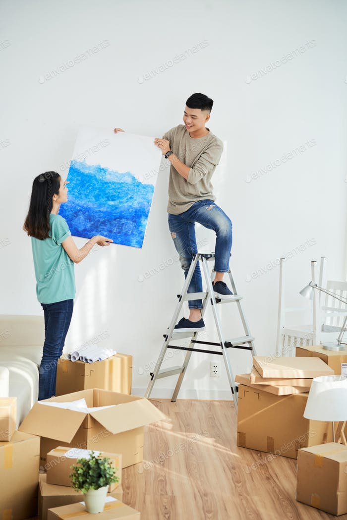 Woman helping man to hang picture
