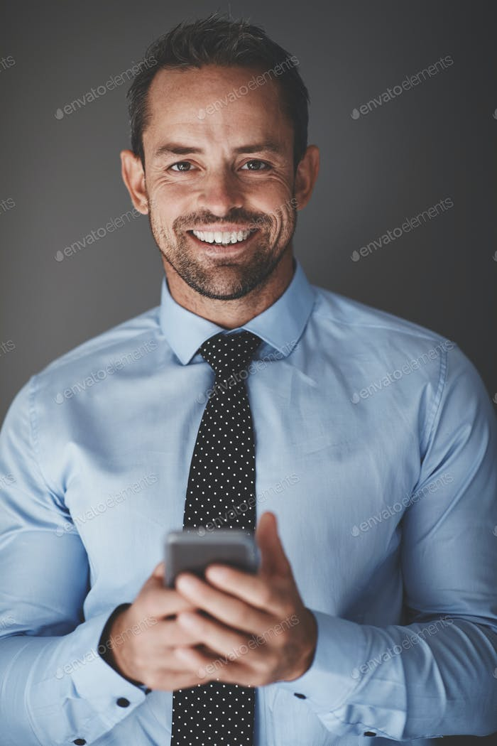 Smiling young businessman using his cellphone against a gray background