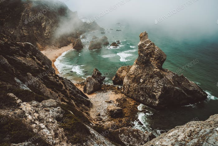 Sentra, Portugal. Moody foggy weather at Praia da Ursa beach on morning. Rough Atlantic Ocean