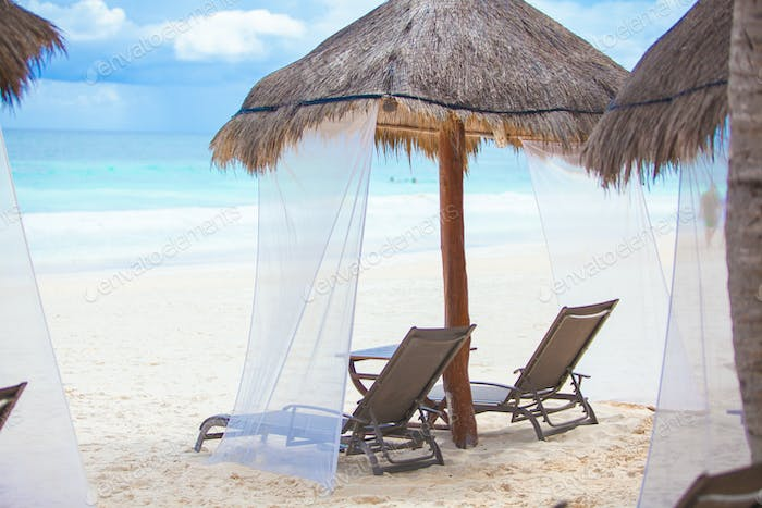 Beach loungers under thatched umbrellas on tropical plage