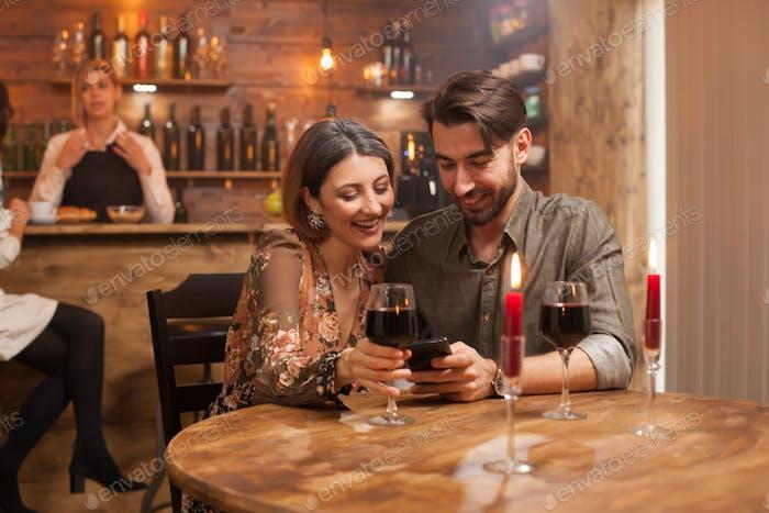 Paar lachen zusammen beim Blick auf sein Handy und trinken Wein auf ihre romantische Verabredung