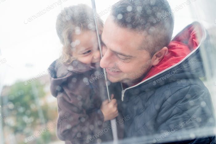 Young father holding daughter under the transparent umbrella.