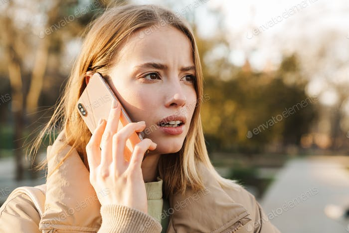 Portrait of scared blonde woman wearing jacket talking on cellphone
