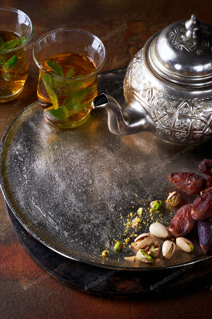 Tea with mint in arab style and dates background.
