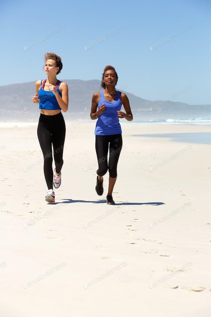 Ganzkörper zwei gesunde Frauen laufen am Strand