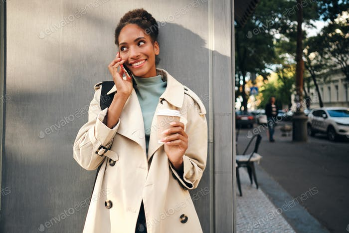Pretty African American girl in stylish trench coat with coffee happily talking on cellphone outdoor