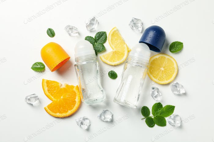 Body deodorants roll-on, leaves, citrus and ice on white background
