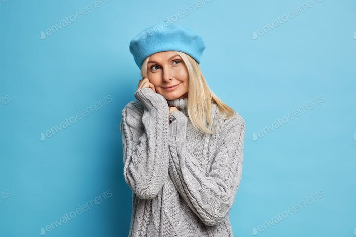Photo of good looking middle aged woman has dreamy pensive expression wears cozy winter grey sweater