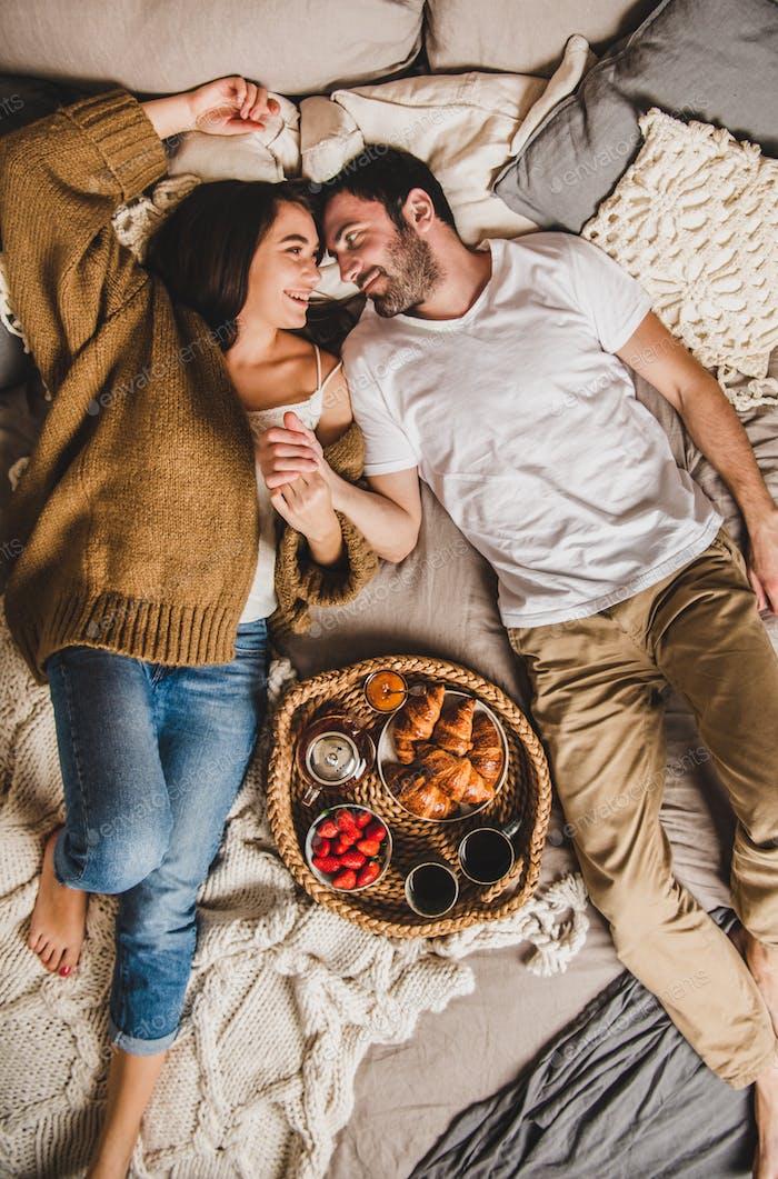 Glückliche lächelnde Paar mit Frühstück im Bett und Hand in Hand