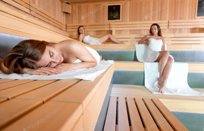 People relaxing in the sauna female friendship and spa treatment