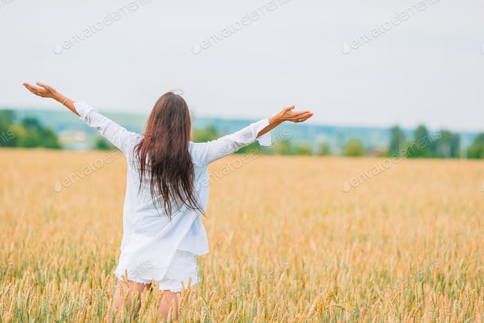 Romantic woman walking in golden fields of wheat