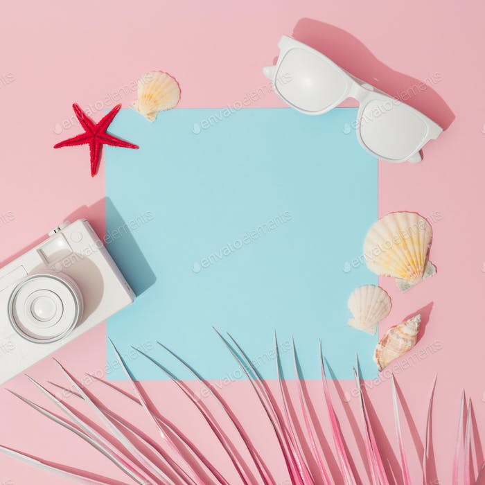 Beach accessories and palm leaves on pastel pink and blue background with copy space