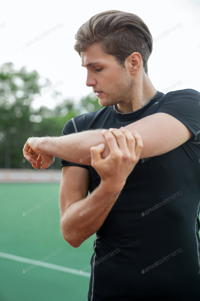 Young male athlete make stretching exercises outdoors