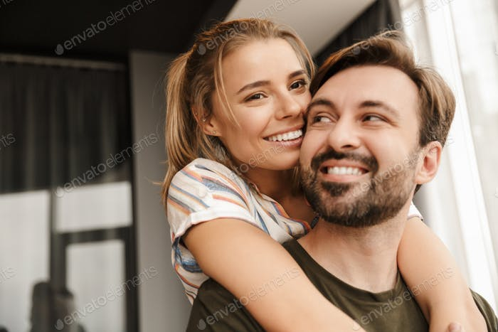 Photo of romantic cute couple smiling and hugging while standing