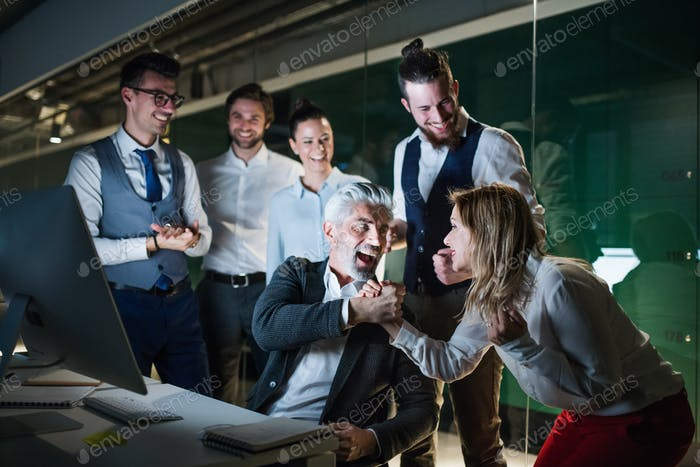A group of business people with computer in an office, expressing excitement