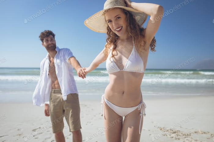 Young Caucasian couple holding hand while standing at beach. They are smiling and looking at camera
