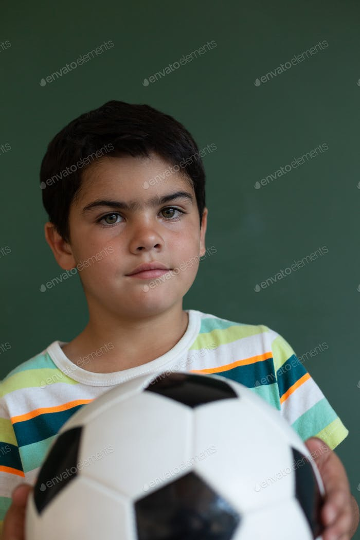Schoolboy with a football standing in front of the blackboard in classroom at elementary school
