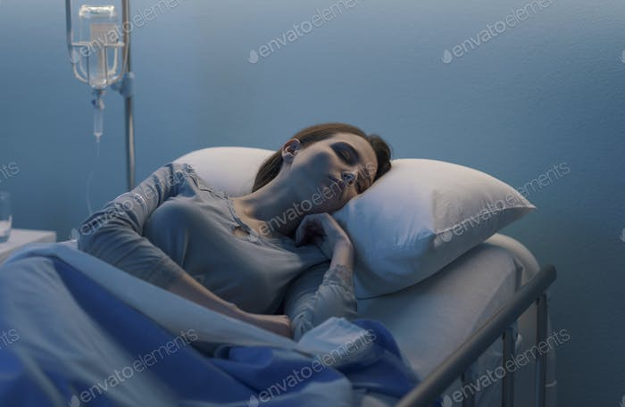 Woman lying in the hospital bed and sleeping with IV drip