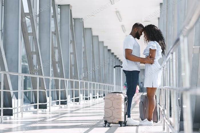African couple hugging tight after long separation in airport