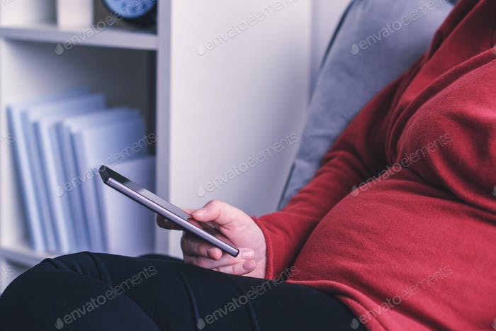 Relaxed pregnant woman using smart phone