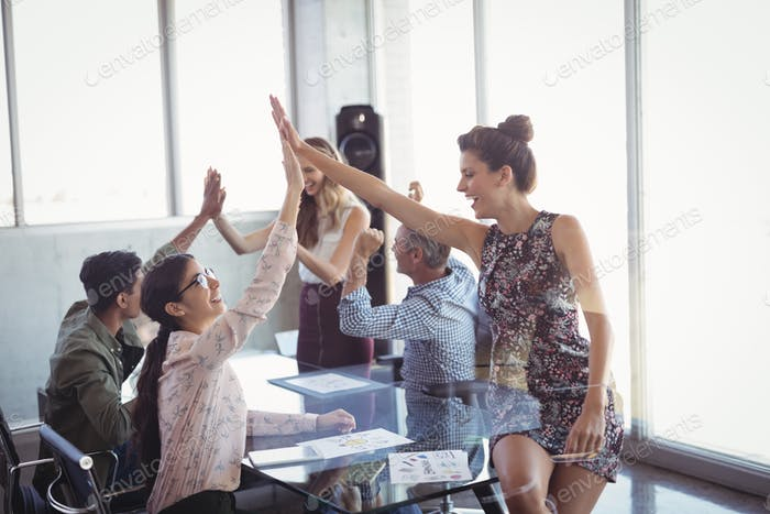 Happy business colleages giving high five at creative office
