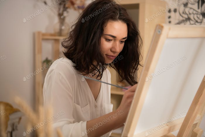 beatifull female artist drawing the picture at the studio